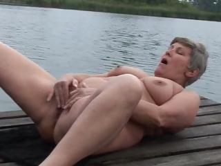 granny is pushing dildo outdoors